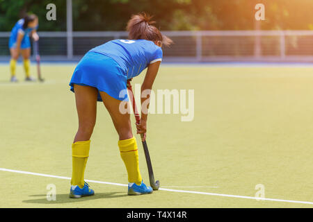 Young female field hockey player with stick on the pitch. - Stock Photo