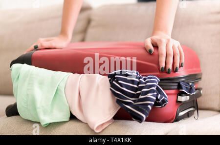 Woman trying to close full suitcase, packing for vacation - Stock Photo