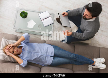 Desperate woman crying, talking to psychologist at therapy session - Stock Photo