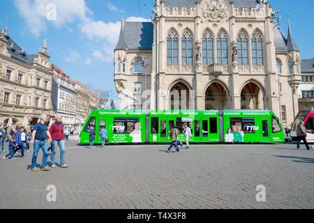 Erfurt, Germany. April 7, 2019. Beautiful old architecture and a modern green tram in the city center - Stock Photo
