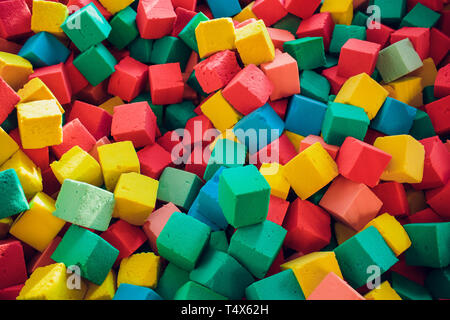 Many colorful soft blocks in a kids' pool at a playground. Bright multi-colored soft cubes, geometric toys. Multicolored background. - Stock Photo