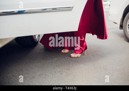 Legs of girl getting out of old auto. young woman in high heels shoes. Chauffeur opening door of vintage automobile for female passenger. - Stock Photo