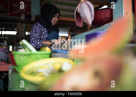 Indonesia, Aceh, December 18, 2018: A rujak trader is preparing a salad order at Gle Geulungku. Rujak is sold for Rp. 5,000, - per portion. - Stock Photo