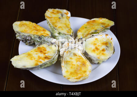 Cheese grilled oyster on dish with dark background - Stock Photo