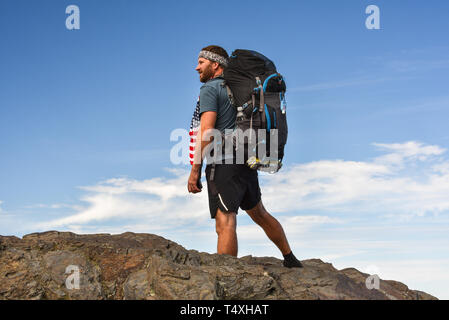 Rugged male backpacker hiking on Appalachian Trail, with pack, in the Great Smoky Mountains National Park in autumn, outside Gatlinburg, TN, USA - Stock Photo