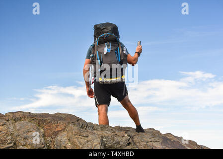 Male backpacker hiking on Appalachian Trail, taking photo with smart cell phone, Great Smoky Mountains National Park, outside Gatlinburg, TN, USA - Stock Photo