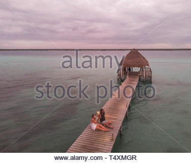 girls sits on wood bridge - Stock Photo
