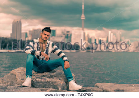 man sits on rock by river - Stock Photo