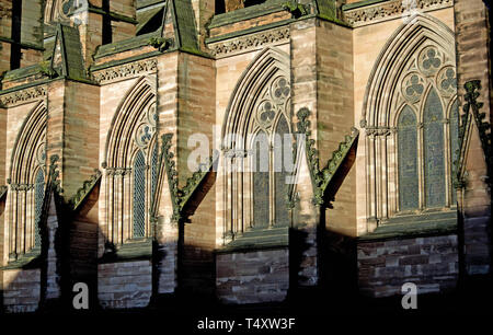 Partial view of the exterior of the medieval Lichfield Cathedral in Staffordshire (UK) showing four identical arched windows and buttresses. - Stock Photo