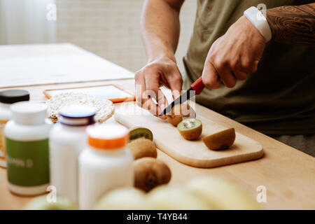 Sportsman wearing white fitness tracker cutting kiwi - Stock Photo