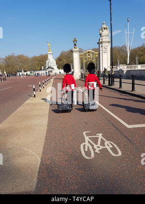 London, United Kingdom, April 14th, 2019. Two men of The Queen's Guard coming to buckingham palace with their luggage - Stock Photo