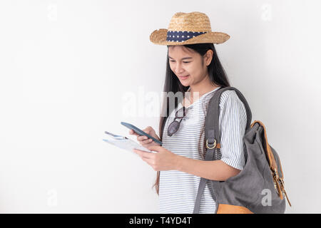 Asian woman traveler backpacker wear sunglasses use map to search for route location of place with gps on white background,Technology in lifestyle - Stock Photo
