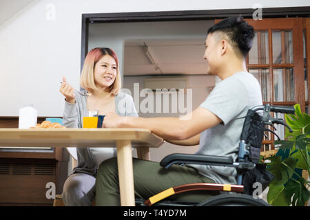 Asian couple breakfast at home.wife holding hand and encourage disabled husband sitting in wheelchair at kitchen table.couple in home concept - Stock Photo