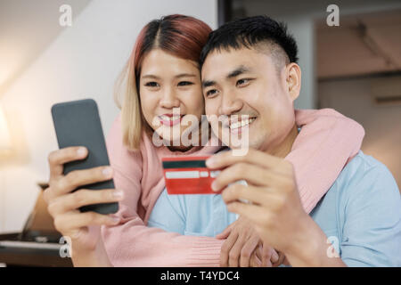 Asian couple use mobile shopping online with credit card together in living room at home.couple in home concept - Stock Photo