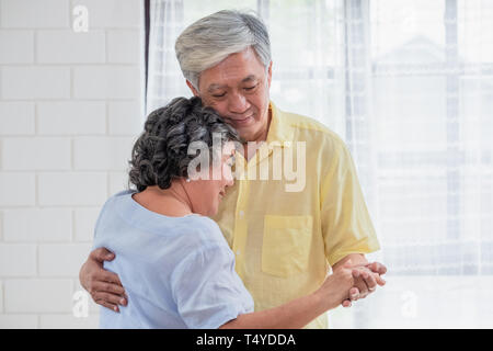asian seniors couple enjoy dancing in living room at home.aging at home concept - Stock Photo