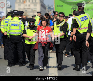 An Extinction Rebellion demonstrator is carried away by police on Waterloo Bridge in London. - Stock Photo