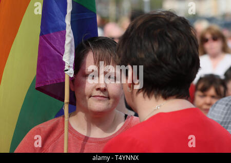 DUP leader Arlene Foster (right) speaks with Sara Canning (left), the partner of 29-year-old journalist Lyra McKee, at a vigil in Londonderry, Northern Ireland, following her death last night after guns were fired and petrol bombs were thrown in what police are treating as a 'terrorist incident'. - Stock Photo