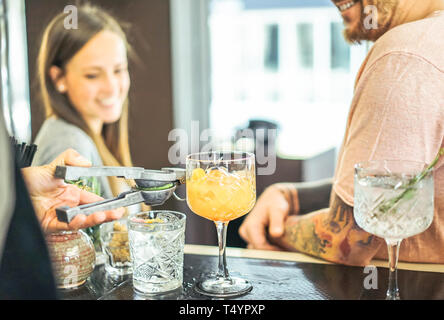 Bartender preparing cocktails pouring out lime - Happy friends waiting for drinks at counter in american bar - People,entertainment, lifestyle concept - Stock Photo