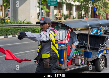 traffic directing marshall in the centre of Bangkok city in Thailand with a tuk tuk in the background on a busy street in the centre of town. - Stock Photo