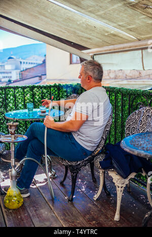 A middle-aged man dressed casually is smoking hookah (shisha) while sitting at an old wooden balcony looking extremely relaxed. - Stock Photo