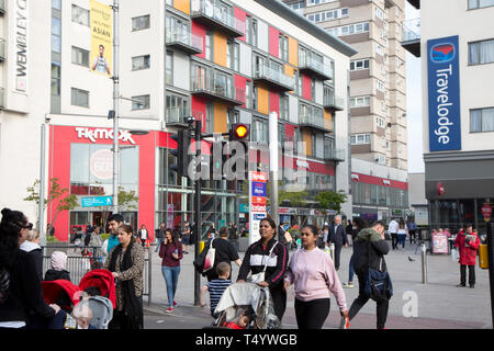 Pedestrians crossing High Road, Wembley, in front of a modern shopping and housing development at Wembley Central. - Stock Photo