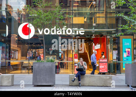 Young woman sitting outside a vodafone store in Sydney talking on her mobile phone whilst working on her laptop,Sydney,Australia - Stock Photo