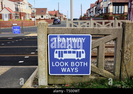 Tramway look both ways sign white on blue background attached to concrete fencing at ltram crossing in Anchorsholme, Blackpool, Lancashire uk - Stock Photo