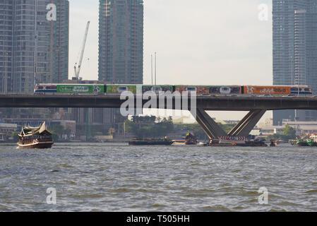 BANGKOK, THAILAND - JANUARY 02, 2019: The train of the 'BTS SkyTrain'  land subway on the bridge through Chao Phraya River river - Stock Photo