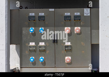 Outdoor weatherproof electrical plug sockets on an electrical distribution panel - Stock Photo