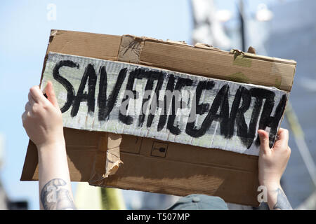 Extinction rebellion protest in London. A sign saying 'Save the earth' is held up. - Stock Photo