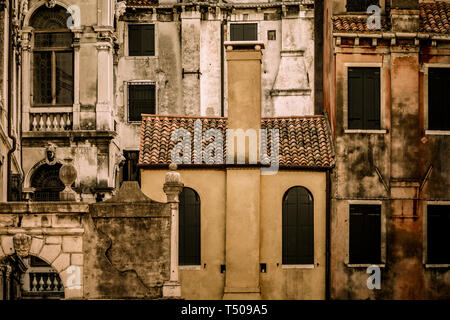 The weathered facades of old buildings in Venice Italy show the ravages of time on their exterior walls. - Stock Photo
