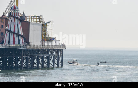 Brighton, UK. 19th Apr, 2019. A water skier heads around Brighton Palace Pier as visitors flock to the seaside to enjoy the Good Friday sunshine as temperatures reach the mid twenties along the South Coast Credit: Simon Dack/Alamy Live News - Stock Photo