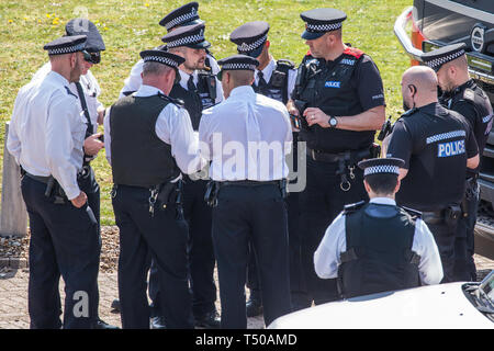 London, UK. 19th April, 2019. A group of senior police officers meets alongside the main motorway approach to Heathrow airport following a small protest earlier by Extinction Rebellion Youth. A large police presence is evident around the airport but so far any disruption feared by the airport authorities from Extinction Rebellion climate change activists has been symbolic rather than material. Credit: Mark Kerrison/Alamy Live News - Stock Photo