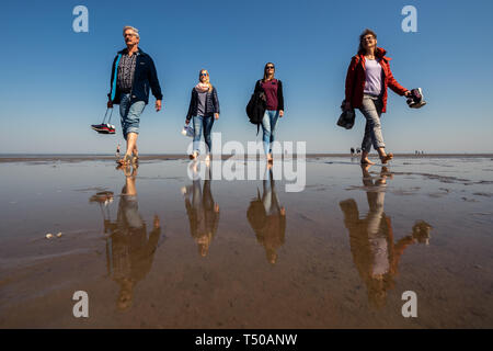 Cuxhaven, Germany. 19th Apr, 2019. The Dreyer family from Hesse takes a walk on the beach of Cuxhaven Döse during their holiday when the weather is fine. Credit: Mohssen Assanimoghaddam/dpa/Alamy Live News - Stock Photo