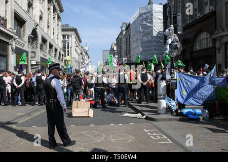 Oxford Circus, London, UK. 19th Apr, 2019. A large number of police presence in Oxford Circus as they prepare to remove environmental activists from Extinction Rebellion movement group from the site. According to the Met Police, nearly 700 activists have been arrested since the demonstration started on 11 April 2019. Credit: Dinendra Haria/Alamy Live News - Stock Photo