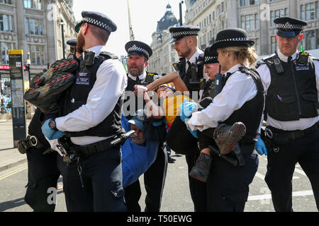 Oxford Circus, London, UK. 19th Apr, 2019. An environmental activist is arrested by the police in Oxford Circus on the fifth day of the climate change protest by the Extinction Rebellion movement group. A large number of police presence around the pink yacht as they un-bonding the activist who glued themselves and the police prepare to remove them from the site. According to the Met Police, nearly 700 activists have been arrested since the demonstration started on 11 April 2019. Credit: Dinendra Haria/Alamy Live News - Stock Photo