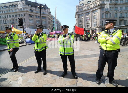 Police cordon seen during the demonstration. Environmental activists from Extinction Rebellion movement occupy London's Oxford Circus for a 5th day. Activists parked a pink boat in the middle of the busy Oxford Circus road junction blocking the streets and causing traffic chaos. - Stock Photo