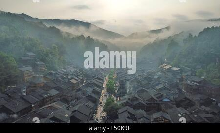Liping. 20th Apr, 2019. Aerial photo taken on April 20, 2019 shows the fog-shrouded Dong village of Zhaoxing, Liping County, southwest China's Guizhou Province. Credit: Ou Dongqu/Xinhua/Alamy Live News - Stock Photo