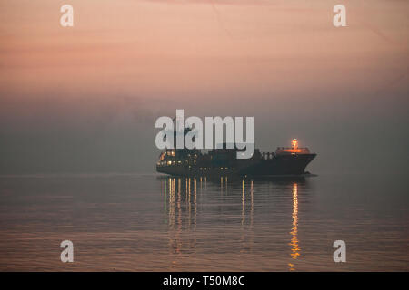 Cobh, Cork, Ireland. 20th April, 2019. Container ship Oeland makes her way slowly through the mist and fog at Cobh as she steams through the harbour towards Tivoli Docks in Cork City where she will unload her cargo. Credit: David Creedon/Alamy Live News - Stock Photo