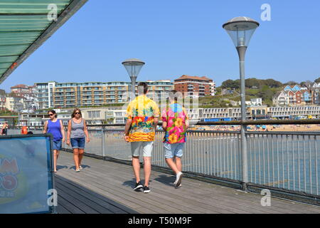 Boscombe, Bournemouth, Dorset, UK. 20th Apr, 2019. Record breaking Easter weather and people flock to the coast for the day to start their summer early. Two young men in brightly coloured Hawaiian shirts on the pier. Credit: Paul Biggins/Alamy Live News - Stock Photo