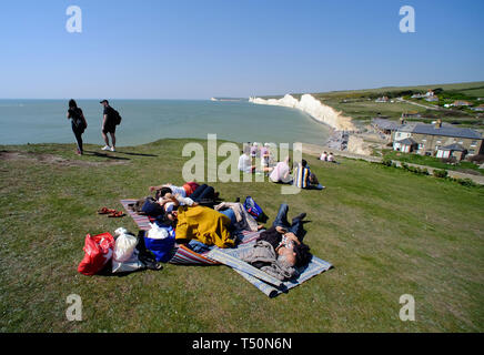 Birling Gap, East Sussex, UK. 20th April 2019. The unseasonably warm weather has seen thousands of tourists flock to the iconic Seven Sisters chalk cliffs near Eastbourne, East Sussex, many of whom take dangerous selfieis on the unstable cliff edge. One man was seen dangling a small child in his arms as he peered over the sheer drop. The cliffs are up to 400 foot high and are a well known suicide spot. © Peter Cripps/Alamy Live News - Stock Photo