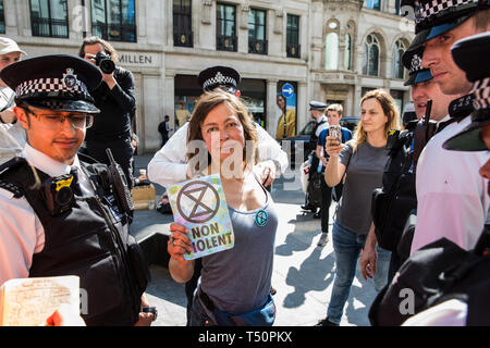 London, UK. 20th April 2019. Police officers arrest writer Jay Griffiths from Extinction Rebellion who had taken part in a lock-on at Oxford Circus following a policing operation to clear it of protesters earlier in the day. The heart of London's shopping district was blocked again for around two hours by the lock-ons on the sixth day of International Rebellion activities to call on the British government to take urgent action to combat climate change. Credit: Mark Kerrison/Alamy Live News - Stock Photo