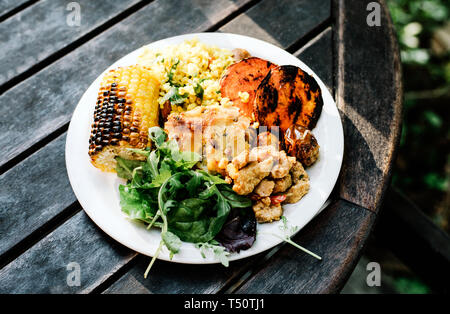 A full plate of vegan and vegetarian buffet foods on a table at a restaurant in Stockholm, Sweden - Stock Photo