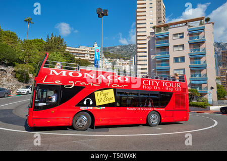 MONTE CARLO, MONACO - AUGUST 21, 2016:  Monte Carlo street curve with formula one red and white signs and Monaco red touristic bus in a sunny summer d - Stock Photo