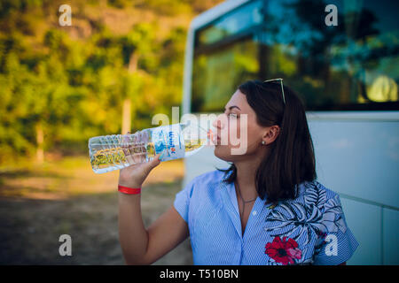 woman drinking water after running outdoors on the background of the bus, tourist. - Stock Photo