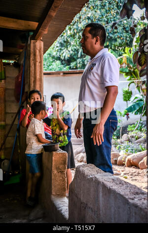 latin man standing with children in background in Guatemalan house
