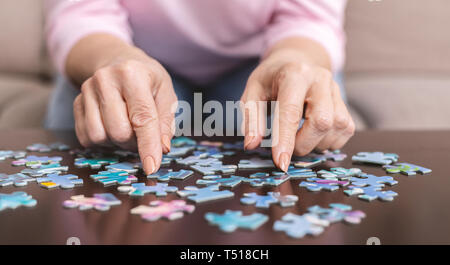 Elderly woman hands doing jigsaw puzzle closeup - Stock Photo