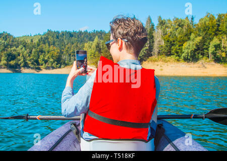 Selfie on lake. Young woman taking self portrait with smart phone in kayak on Lokvarsko lake in Gorski kotar, Croatia. Woman enjoying adventurous - Stock Photo