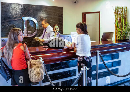 Cartagena Colombia El Laguito Hotel Dann hotel front reservation reception desk counter Hispanic resident residents man woman guests employee employee - Stock Photo