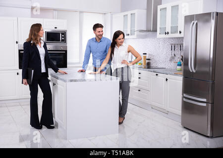 Professional Real Estate Agent Showing Refrigerator In House To A Young Couple - Stock Photo